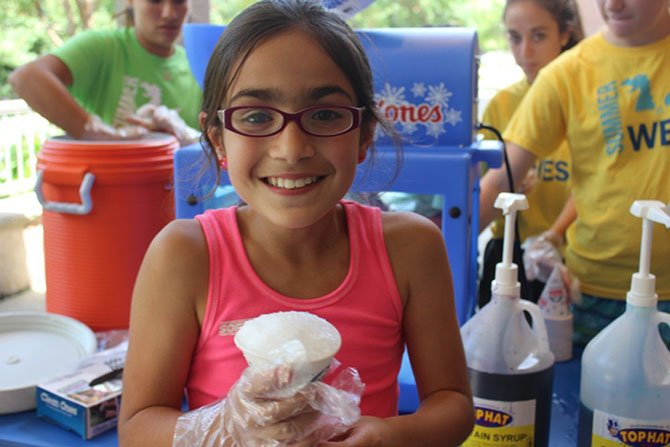 Emelia Isola, 10, helps to sell snow cones during Summer at WES camp to benefit House With A Heart, a senior pet Sanctuary in Gaithersburg.