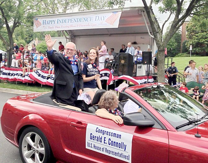"U.S. Rep. Gerry Connolly (D-11), his wife ""Smitty,"" and daughter Caitlin greet well-wishers along the City of Fairfax Fourth of July parade route.  Connolly and his family celebrated at parades in Fairfax, Dale City and Lake Barcroft."