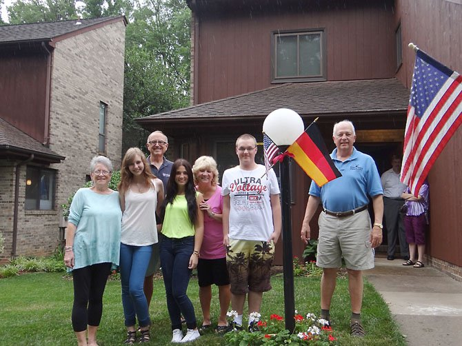 From left, Elaine Montgomery, Olivia Kühne, Alan Montgomery, Özge Kayalar, Becky Biondi, Dominick Zeitz and Dan Biondi pose with the American and German flags outside the Montgomery's home in Reston.