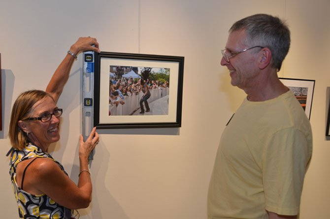 Mercia Hobson and Jeff French hang a photo which will be on exhibit at ArtSpace Herndon.