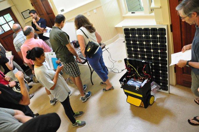 Visitors to the Reston Energy Fair examine a portable solar powered generator Sunday, July 14.