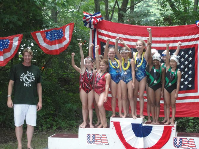 The Kingston Chase (Sydney Douglas, Scout McClain, Mackenzie Kleczynski, Casey Mills), Hiddenbrook (Maddie Morin, Audrey Ferguson, Alyssa Landrum, Kate Keane) and Herndon Community Center (Sophia Lee, Shreshtha Peter Rai, Rachel Sim, Chloe Thomson) 8 & Under Girls 100 Meter Freestyle Relay teams pose with Josh Davis on the Herndon Olympics podium.