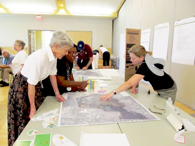 Joy Koeppen, far right, points out a possible location for a handicapped-accessible playground on a map of Van Dyck Park to Diane Henn and Vicki Woods during a public workshop at the Sherwood Community Center on Sunday, June 23.