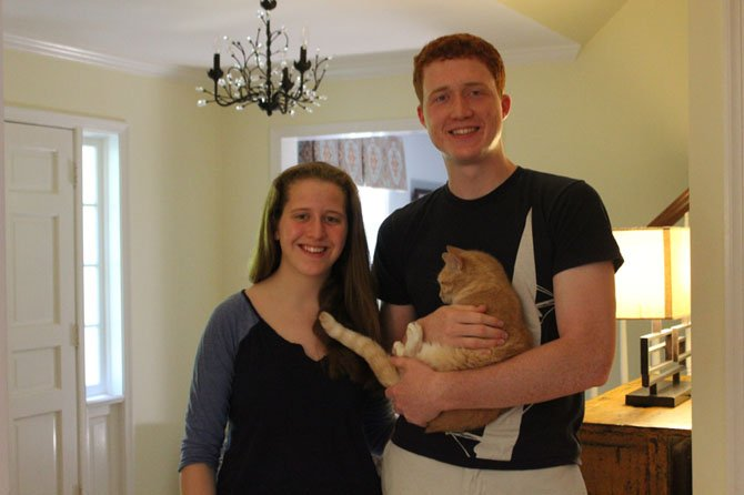 Siblings Caroline and James Bollinger of McLean stand with one of their three cats, Lizzie.