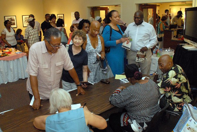 Patrons queue up to have their books signed by three of the authors, James Henson, Sr., Char McCargo Bah and Christa Watters.