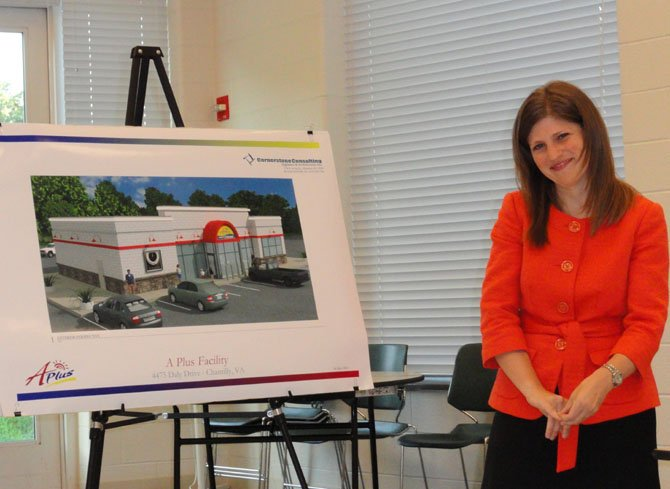 Sara Mariska stands next to an artist's rendition of the new convenience store.