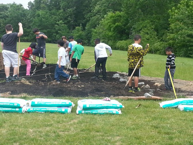 Centreville Elementary fourth-graders work the soil inside their map of Virginia.