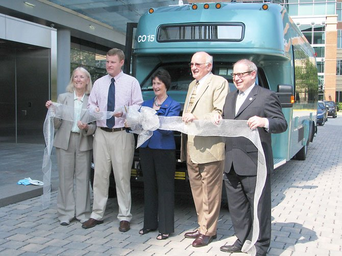 Elected officials cut the ribbon during a ceremony announcing the addition of six new TAGS buses in Alexandria July 17. From left, Del. Vivian Watts (D-39), Supervisor Jeff McKay (D-Lee), Fairfax County Board of Supervisors Chairman Sharon Bulova (D-at-large), TAGS official Jack Mutterelli, and Del. Mark Sickles (D-43).