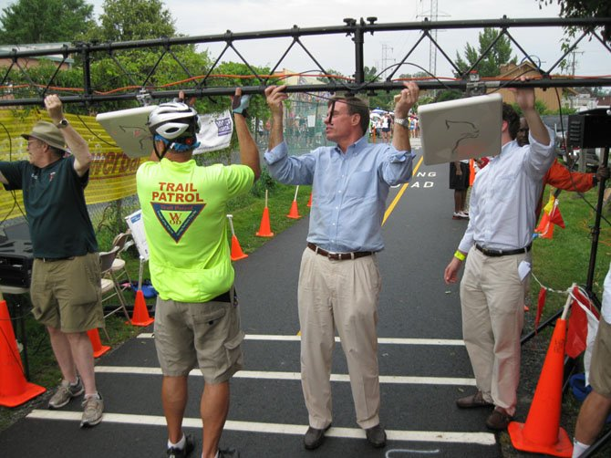 Sen. Mark Warner, a regular cyclist and W&OD trail-user, helps hoist up the timing bridge before the race begins.