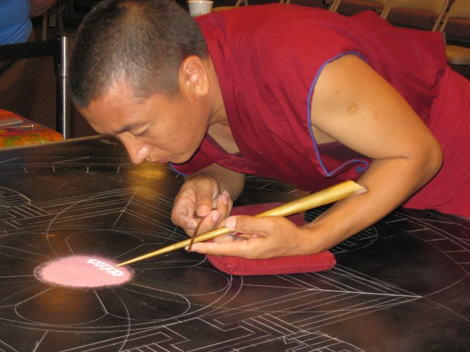 A Tibetan monk uses a chakphur or metal funnel to build the mandala sand painting on the template.