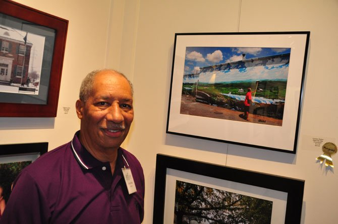 "Photographer Charles Walker took two photos that will be a part of the Herndon 2014 Town Calendar. He is next to one of them, called ""Paint the Sky."""