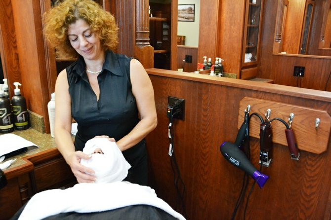 Sibel Ariken, manager of Roosters MGC, applies relaxing steam towels in preparation for the store's signature shave and facial massage.