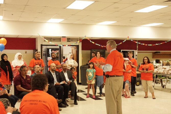Supervisor John Foust (D-Dranesville District) addresses the Herndon Without Hunger volunteers before the start of the first of four food distribution events during Ramadan. Foust has been a long-time supporter and volunteer at the charitable event.
