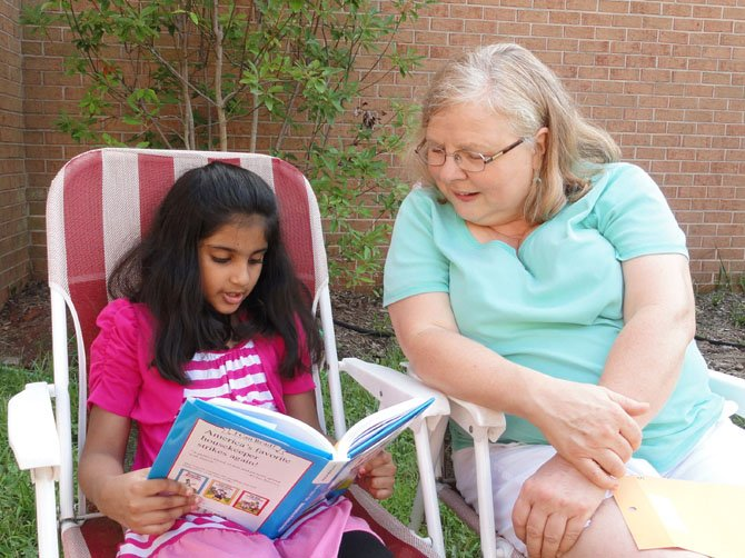 "Rising second-grader Iman Asim reads ""The Adventures of Amelia Bedelia"" with CPC volunteer Darlynne Gendreau."