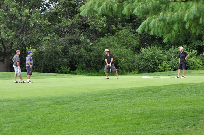 Golfers complete a hole during the annual golf tournament to benefit the Council for the Arts of Herndon Thursday, Aug. 1.