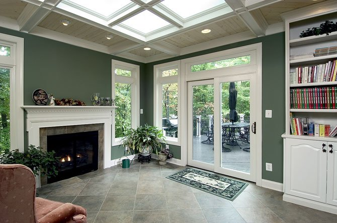 Bringing the outdoors inside: a light-filled sunroom boasting views in all directions opens to a spacious dining deck. The sunroom features a gas fireplace and a custom-designed skylight that fills most of the ceiling. The owners find it an ideal spot for cool weather nature-watching.