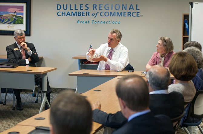 Members of the Dulles Regional Chamber Board of Directors listen as Democratic gubernatorial candidate Terry McAuliffe, center, discusses his top priorities for the commonwealth if he wins this year's election. Also pictured: Don Owens, left, chairman of the chamber's board of directors, and Eileen Curtis, right, the chamber's president and CEO.