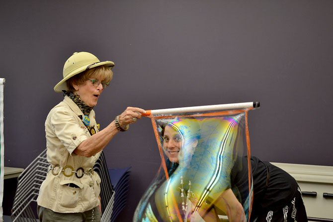 Safari Bingo creates a gigantic bubble around the head of a librarian at a children's event at Burke Centre Library in June 2013. The library was scheduled to be one of two libraries tested with a reorganization plan on Sept. 1. That plan has been put on hold after criticism from library volunteers, staff and patrons.