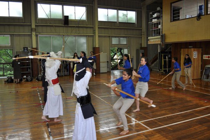 From front, Sophie Fouladi, Christina Amano-Dolan, Ila Sharma, Ayn Kurzenhauser, Asher Berwick and Tatiana Ahmad practice Kendo with students from Eisugakkan Elementary School in Fukuyama Japan.