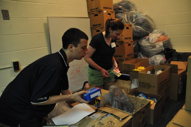 From left, Share volunteers Jack Buttarazzi and Lizzie Gidley sort donated school supplies for Share clients Wednesday, Aug. 14, part of Share's back-to-school drive.