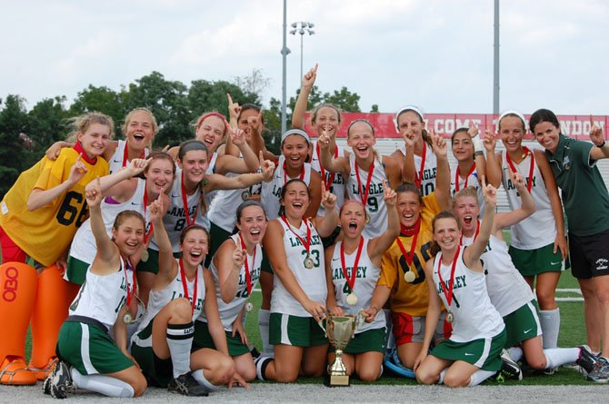 The Langley field hockey team celebrates with the trophy after winning the Herndon Invitational.