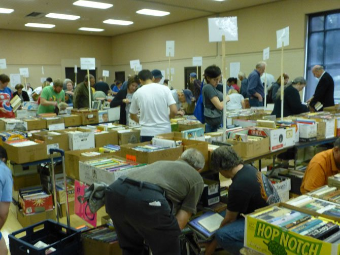A photo from the last year's book sale: The many thousands of individual books and CDs and DVDs have been well sorted and will be displayed in clearly labeled and logical categories.