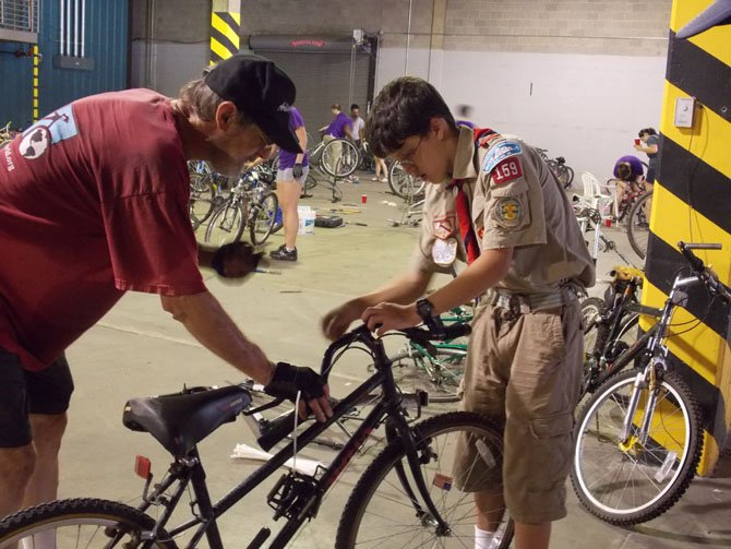 Keith Oberg, head of Bikes for the World, teaches Life Scout Conor Mears how to prepare the donated bikes for shipping.
