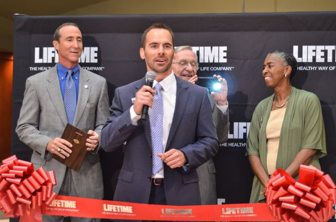 "Miklos Horvath, a general manager at Life Time Fitness, speaks at the grand opening ceremony in Reston. Behind him are Mark Ingrao, Del. Ken Plum (D-36), and Supervisor Catherine M. ""Cathy"" Hudgins (D-Hunter Mill)."