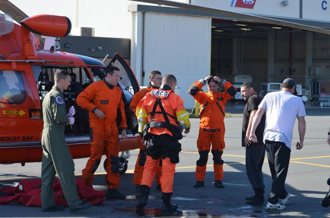 Coast Guard Lt. Brian Ward (third from the right) acted as aircraft commander for the mission to rescue two fishermen (first and second from the right) after their boat mysteriously began sinking.