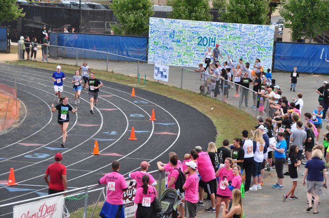 Spectators cheer runners in the Tim Susco 8K as they enter the track at South Lakes High School Saturday, Sept. 21.