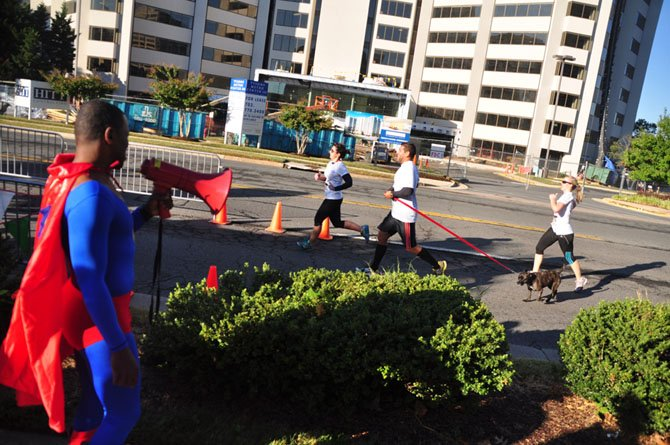 Dan Brazelton, dressed as Superman, cheers runners as they cross the finish line at the 10th annual Super H 5K Sunday, Sept. 22.