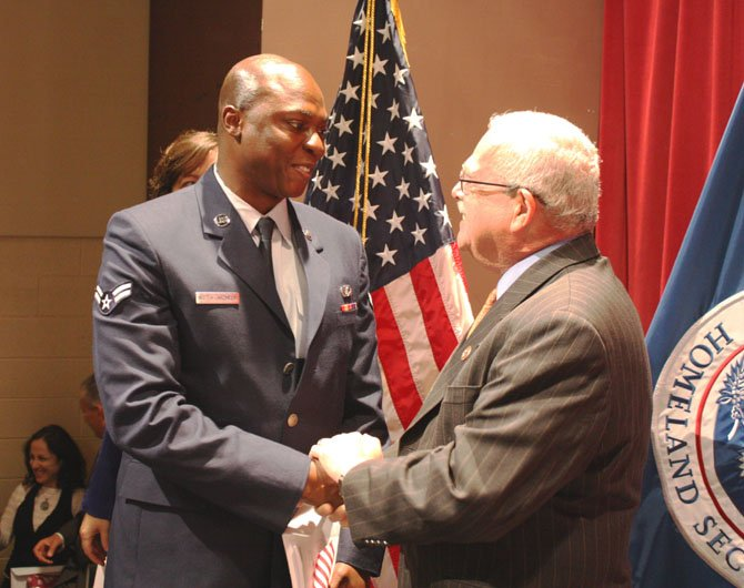 >Class Peter Nketia-Akonnor from Ghana, who serves in the Air National Guard at Joint Base Andrews, smiles proudly as Congressman Gerry Connolly congratulates him on becoming a U.S. citizen.