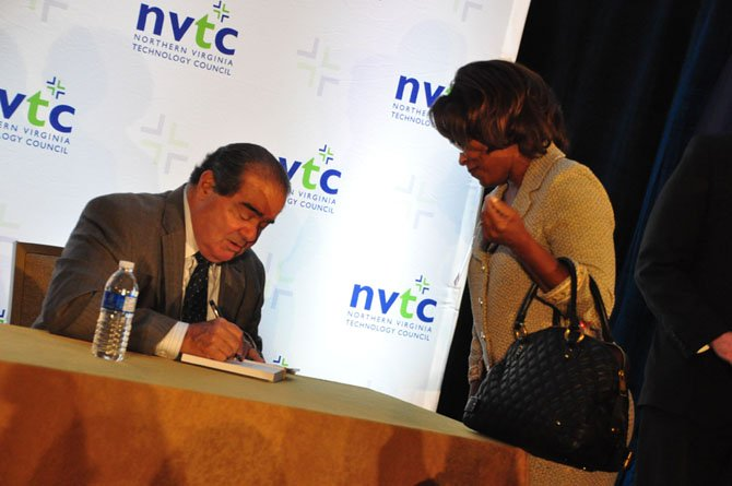 "Associate Justice of the Supreme Court Antonin Scalia signs a copy of his book, ""Making Your Case"" for Karen Smaw Wednesday, Sept. 25 after addressing the Northern Virginia Technology Council."