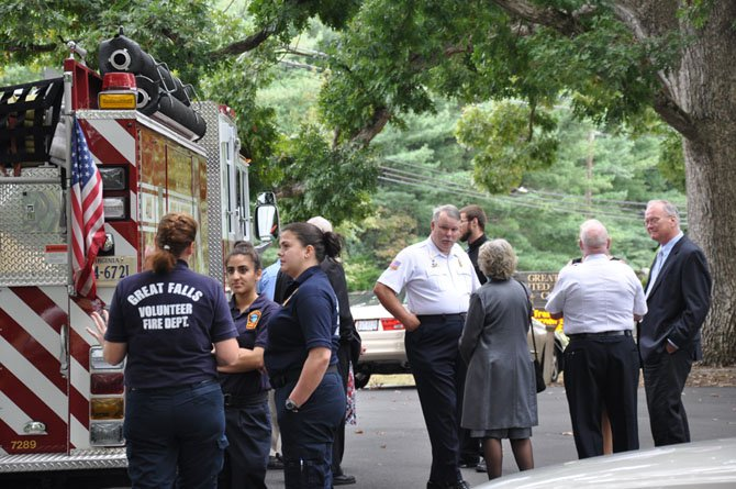 """Members of the Great Falls Volunteer Fire Department, including GF Volunteer Fire Chief Franklin Smith III and former Chief Homer Johns, talk with family members at a memorial service for local volunteer firefighter and Santa representative, Dr. Christopher Earl """"Doc"""" Kennemer."""