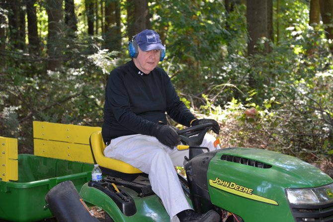 """Neighbor Harold Schroeder was """"just happy to be asked to help,"""" he said. Schroeder brought his John Deere rider to use it in the Work Day at Stuart Road Park in Reston, organized by Boy Scout Ethan McKnight."""
