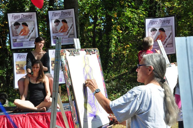 Joan Ferrum tries her hand at painting two models during the annual MPAartfest Sunday, Oct. 6.