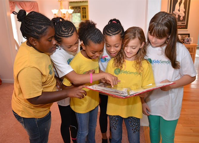 Founding members of Kids Sending Smiles do a little reminiscing as they look over the scrapbook of their non-profit's activities. From left: Laila Tucker, 9, Island Creek Elementary, Adaya Beatrd, 10, Lorton Station Elementary, Tatiana Joseph, 10, Lane Elementary, Alliyah Beard, 11, Lorton Station, Samantha Underwood, 10, Springfield Estates Elementary, Samantha Wenger, 10, Island Creek.