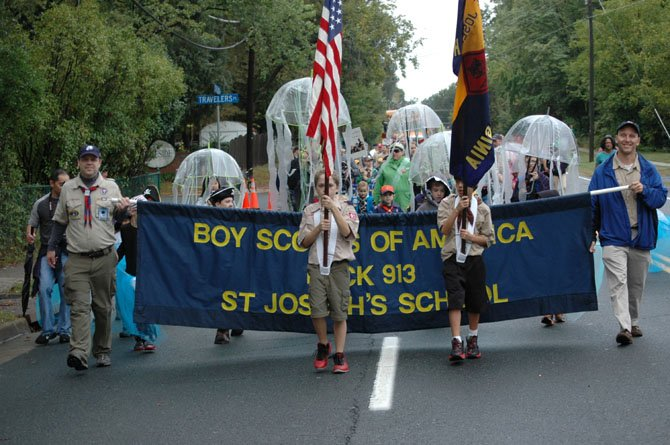 "Cub Scouts of Pack 913 won First Place - Civic Organization: Roan Toole (9) of St. Joseph Cub Scout Pack 913 carries the flag down Elden St. during this year's Herndon Homecoming Parade last Saturday. Dressed as pirates, sharks, jellyfish and octopi in support of this year's ""Sea Swept"" parade theme, Pack 913 won first place in the Civic Association category."