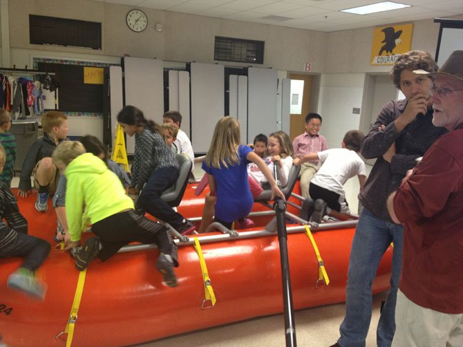 Assistant Principal Mike Casey (far right) with students clambering about in his raft (in which he has logged thousands of white water miles).