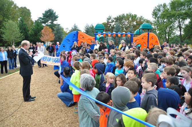 Colvin Run Elementary School Principal Kenneth Junge welcomes students to the ribbon cutting of the school's new playground Wednesday, Oct. 23.
