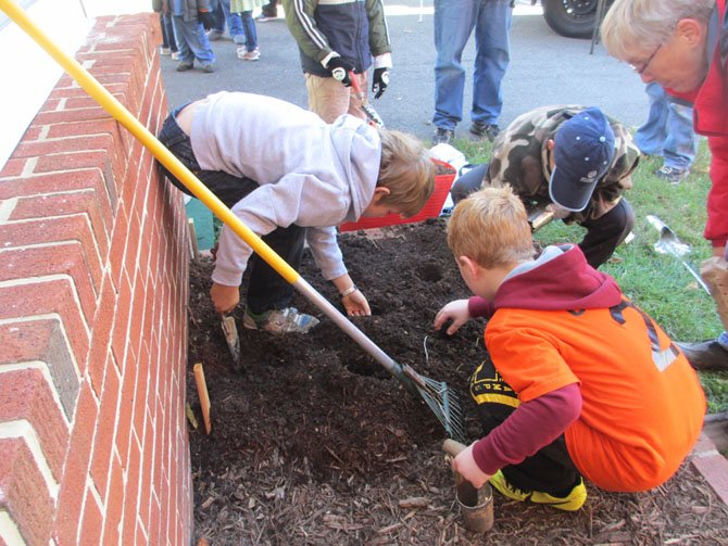 The Ayr Hill Garden Club and farmers market master Sarah Jane Brady helped visiting children to plant spring bulbs at Faith Baptist Church. The church lent the market its grounds for the market season.