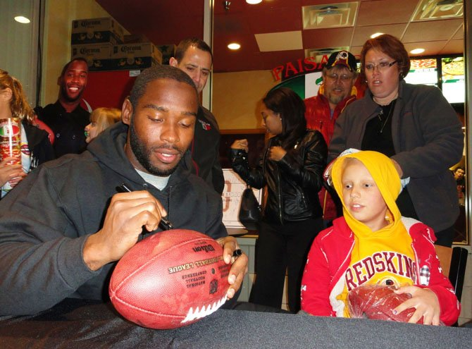 Tara Sankner watches Pierre Garçon autograph a fan's football; in the background are Fouad Qreitem and Craig and Tammy Sankner.