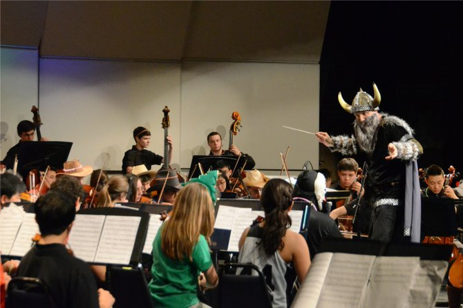 Disguised as the school mascot, the Langley Saxon, Dr. Scott McCormick conducts the Sophomore Orchestra.