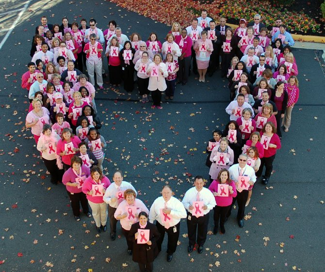 "Northwest Federal Credit Union and Northwest Federal Credit Union Foundation staff gather to display their ""heartfelt hope for a cure"" in support of breast cancer education and awareness on Oct. 25. Special guest Gigi Hyland, Executive Director of the National Credit Union Foundation, joined in the effort, standing at the bottom point of the heart formation."