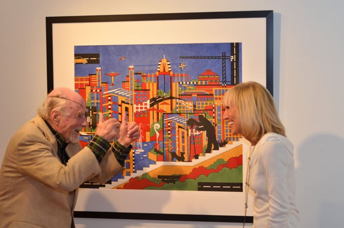 "Reston founder Robert ""Bob"" Simon poses for a photo with Reston artist Dana Scheurer. In the image is a black silhouette of Simon."