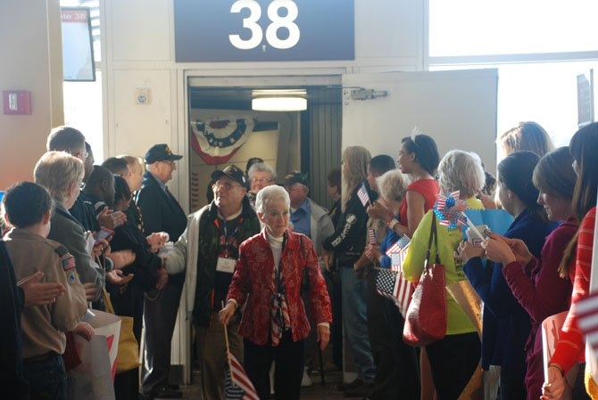 Nearly 300 people gathered at the US Airways terminal to welcome WWII veterans as part of the Honor Flight program.