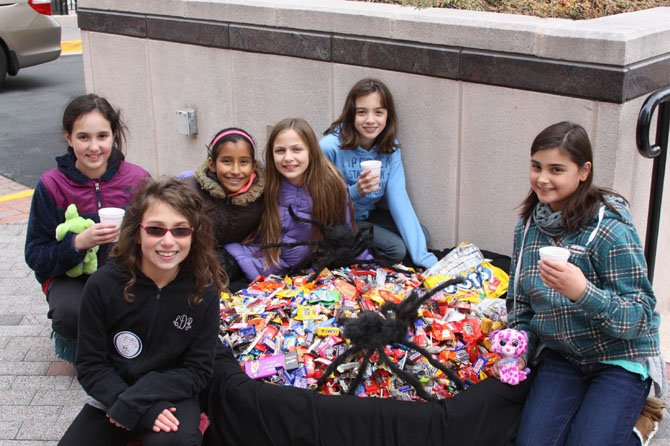 Children posing with some of the candy collected at the 8th Annual Halloween Candy Buy-Back event.