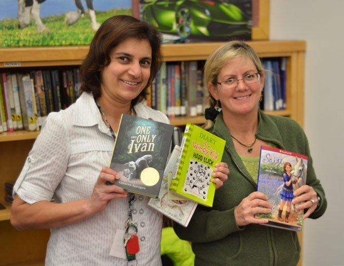 From left, Shermin S. Kapadia and Joanne Lyons, members of the Herndon PTA helped sell books at the Herndon Elementary fall book sale.