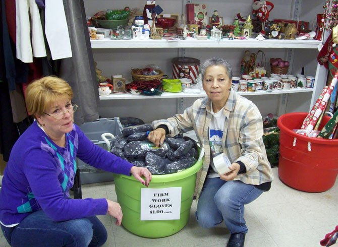 Sheron Flynn, store manager of Lorton's Attic, works with volunteer Audrey Silvia of Springfield to organize a donation of gloves.