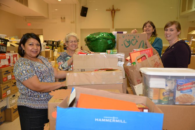 Cornerstones staff and volunteers accept food donations and prepare the boxes the night before the Thanksgiving food distribution at St. John Neumann Catholic Church in Reston. From left: Minnie Orozco, Urgent Needs and Life Skills Program Manager, Gail Greenberg, Board Member and volunteer, Susan Alger, Volunteer and Resource Manager, Embry Rucker Community Shelter, and Alacia Earley, Volunteer and Drives Manager.
